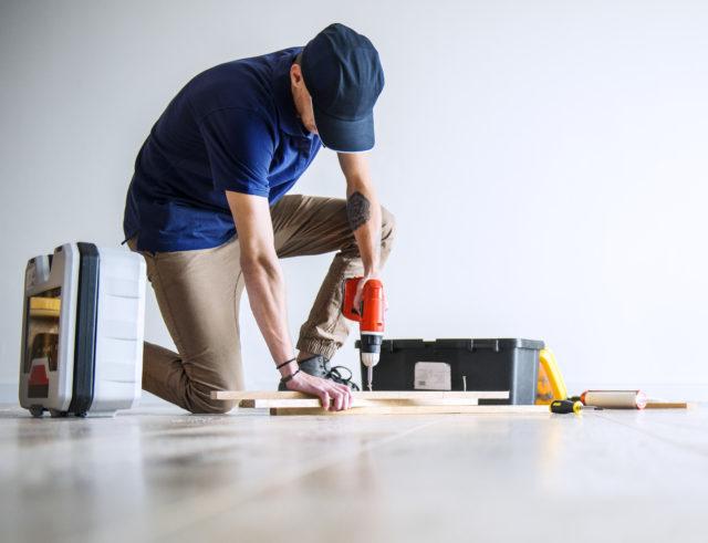 Un homme équipé d'outils réalise des travaux dans une maison