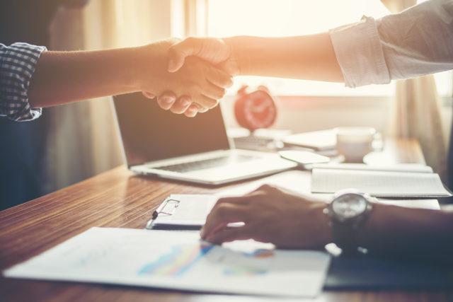 Deux personnes se serrent la main dans un bureau