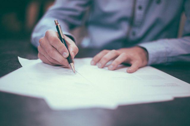 un agent immobilier qui signe un mandat assis à un bureau