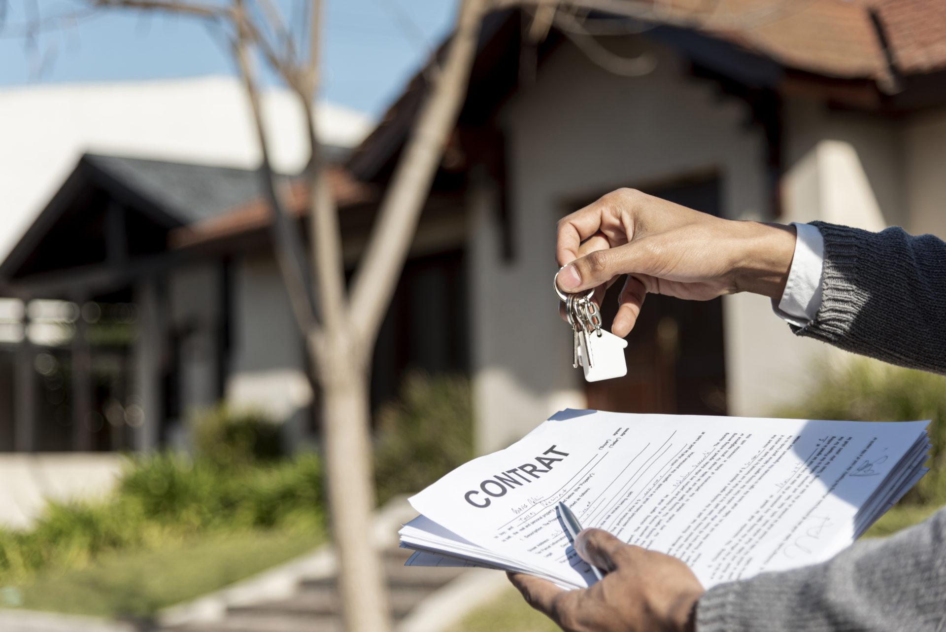 un homme tient un contrat de vente à réméré dans sa main devant une maison