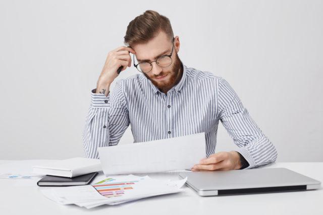un homme en train de choisir son agence immobilière devant des documents