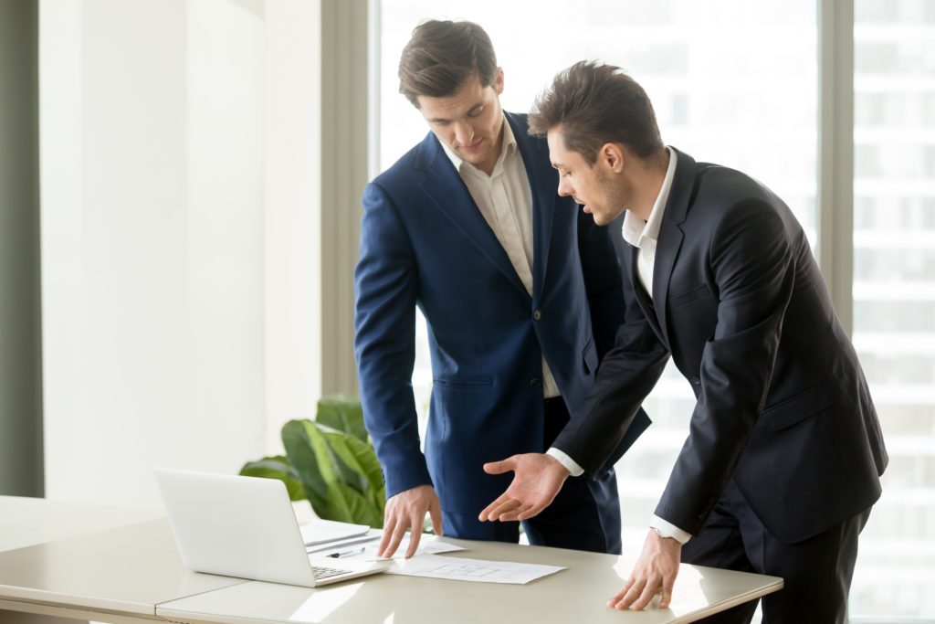 un agent immobilier présente le barème d'honoraires à son client