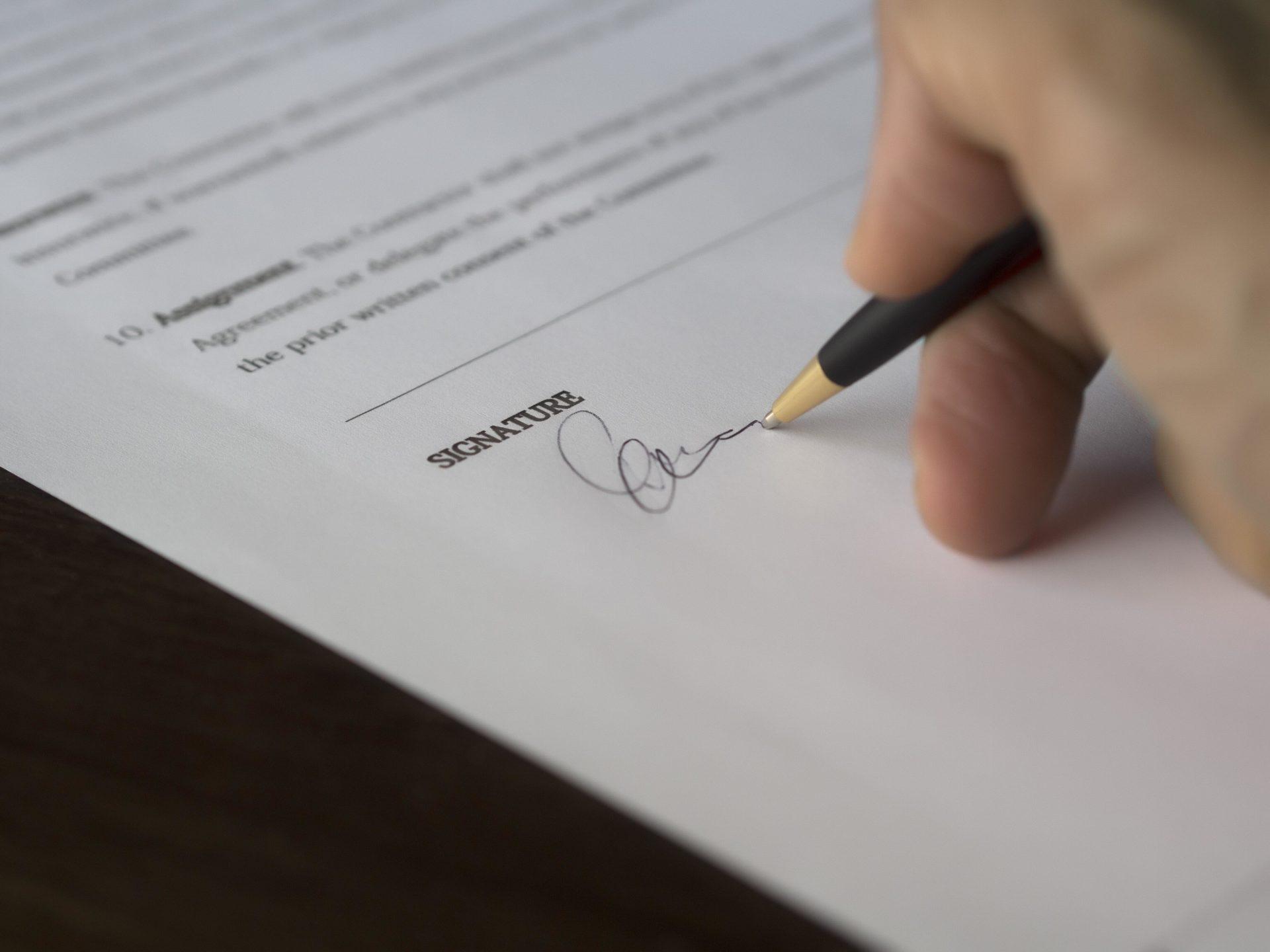 un client signe un mandat de vente immobilière à une agence après acceptation des honoraires
